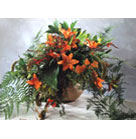 Orange Lilies with Leather Fern and accenetd green in ceramic vase