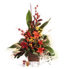 Orange Lilies, Yellow Pompons combined with Red Capsicum and Eucalyptus in straw basket